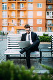 Young businessman sitting at the bench and working on laptop and drink morning coffee. Young businessman sitting at the bench and working on laptop Royalty Free Stock Photos