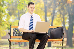 Young businessman sitting on bench and working on laptop in a pa. Young businessman sitting on a bench and working on a laptop in a park Stock Photo