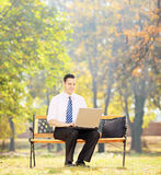 Young businessman sitting on a bench and working on a laptop in Stock Images