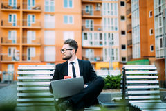 Young businessman sitting at the bench and working on laptop and drink morning coffee. Young businessman sitting at the bench and working on laptop Royalty Free Stock Images