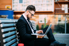 Young businessman sitting at the bench and working on laptop and drink morning coffee. Young businessman sitting at the bench and working on laptop Stock Photography