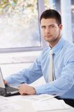 Young businessman sitting in bright office Stock Photo