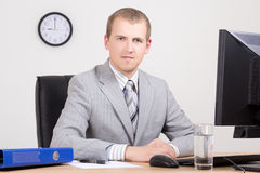 Young businessman sitting in bright office Royalty Free Stock Images