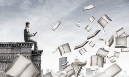 Man using smartphone and many books flying in air Stock Images