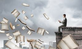 Man using smartphone and many books flying in air. Young businessman sitting on building edge with smartphone in hands Royalty Free Stock Images