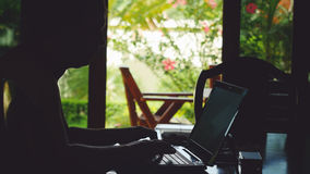 Young businessman sitting in bungalow and working on laptop while traveling Stock Photography