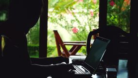 Young businessman sitting in bungalow and working on laptop while traveling. stock footage