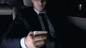 Young businessman sitting on car back seat and using smartphone, night city view. Stock footage stock video