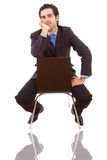 Young businessman sitting on chair. Against white background Royalty Free Stock Photography
