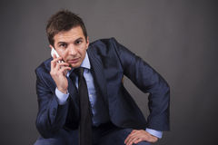 Young businessman sitting on a chair and holding a mobile phone Stock Photography
