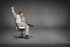 Young businessman sitting in chair with laptop. Business, internet and technology concept - young businessman sitting in chair with laptop Stock Photos