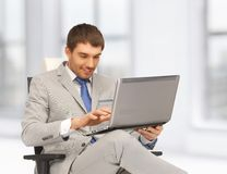 Young businessman sitting in chair with laptop Royalty Free Stock Image