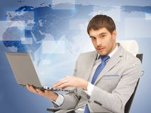 Young businessman sitting in chair with laptop Royalty Free Stock Photo