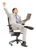 Young businessman sitting in chair with laptop. Picture of young businessman sitting in chair with laptop Royalty Free Stock Photos