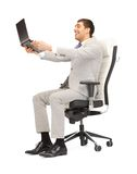 Young businessman sitting in chair with laptop Stock Photo