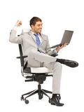 Young businessman sitting in chair with laptop. Picture of young businessman sitting in chair with laptop Stock Photo