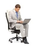 Young businessman sitting in chair with laptop Royalty Free Stock Images