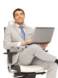 Young businessman sitting in chair with laptop Royalty Free Stock Photos