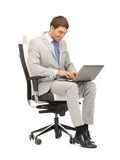 Young businessman sitting in chair with laptop Stock Photography