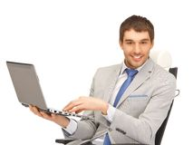 Young businessman sitting in chair with laptop Stock Photos