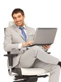 Young businessman sitting in chair with laptop Royalty Free Stock Photography
