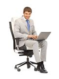 Young businessman sitting in chair with laptop Stock Image