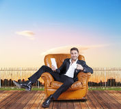 Young businessman sitting in chair outdoor. Watching smart phone Royalty Free Stock Photography