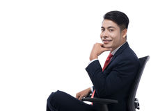 Young businessman sitting on chair over white background, lookin. Young businessman sitting in swivel chair over white background, thinking Stock Photo