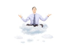 Young businessman sitting on a cloud and gesturing with his hand Royalty Free Stock Photography