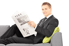 Young businessman sitting on a couch with newspaper Stock Image