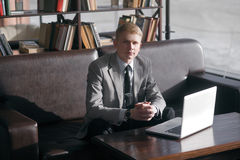 Young businessman sitting at desk with laptop stock photo