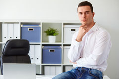 Young businessman sitting on desk Royalty Free Stock Images