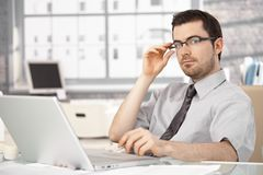 Young businessman sitting at desk using laptop royalty free stock images