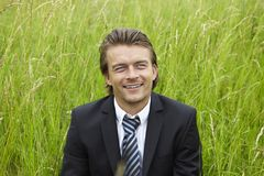 Young businessman is sitting in a field Stock Photography