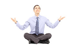 Young businessman sitting on a floor and gesturing with his hand Royalty Free Stock Images