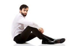 Young businessman sitting on the floor. Royalty Free Stock Photo