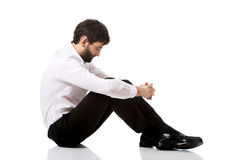 Young businessman sitting on the floor. Stock Photo