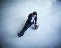 Young businessman sitting on the floor using his laptop Royalty Free Stock Photo