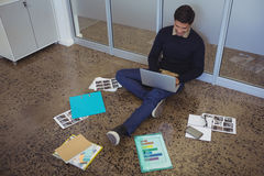 Young businessman sitting on floor while working in creative office Royalty Free Stock Photo