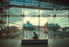Young businessman sitting between glass buildings inside Black Diamond, modern part of Royal Danish Library royalty free stock photos