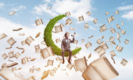 Businessman or student announcing something in loudspeaker and books flying around. Young businessman sitting on green moon and screaming emotionally in Stock Photography