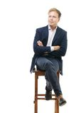 Young businessman sitting on high wooden chair Royalty Free Stock Images