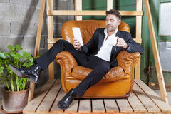 Young businessman sitting in his chair. Watching smart phone Stock Images