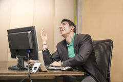 Young businessman sitting at his desk laughing Stock Image