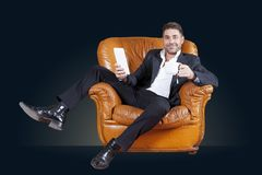 Young businessman sitting in his leather chair. Watching smart phone on black background Stock Photo