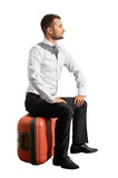 Young businessman sitting on his suitcase Stock Photography