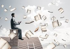 Man using smartphone and many books flying in air Royalty Free Stock Image
