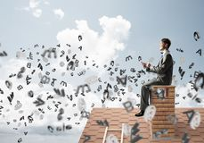Man on brick roof working with smartphone and symbols flying around. Young businessman sitting on house with smartphone in hands Royalty Free Stock Images