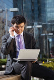 Young businessman sitting with laptop. Royalty Free Stock Photos
