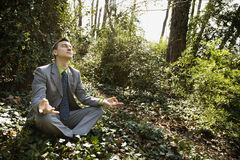 Young Businessman Sitting in Meditation Stock Photo
